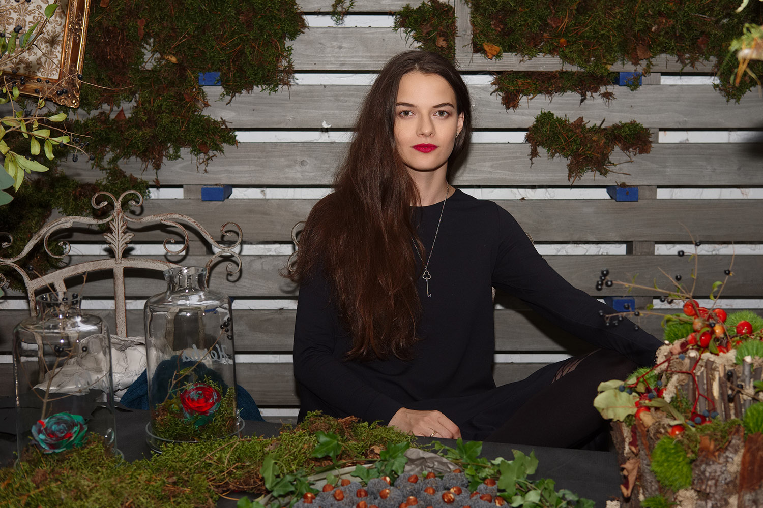 Attractive lady sitting behind herbal table with sweets