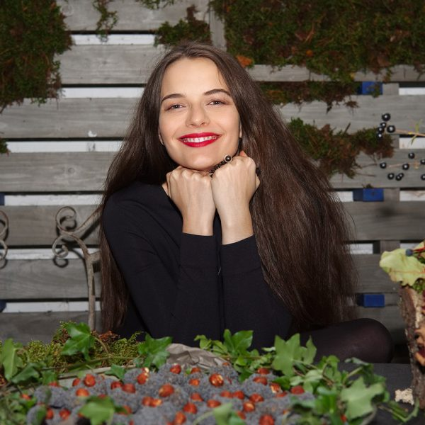Happy lady sitting behind herbal table with sweets